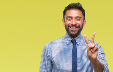 Adult hispanic business man over isolated background smiling with happy face winking at the camera doing victory sign. Number two.