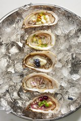 Overhead view of variety oyster shells placed on ice container