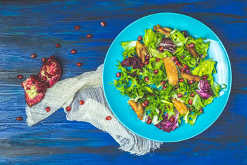 Fresh healthy salad with lettuce, chicken and pomegranate in blue plate