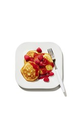 Overhead view of pancake with raspberry served on plate