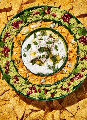 Close up of various types of dips arranged in bowl over tortilla chips