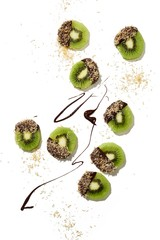 Slices of kiwi covered with chocolate and coconut over white background
