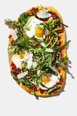 Fried egg, flatbreads with nduja and mustard greens on white background