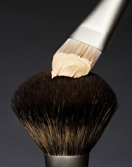 Close up of makeup brush and cream against black background