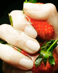 Close up of woman's hand squeezing strawberries