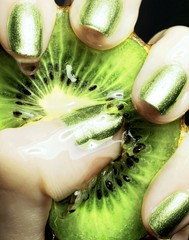 Close up of woman's hand squeezing kiwi