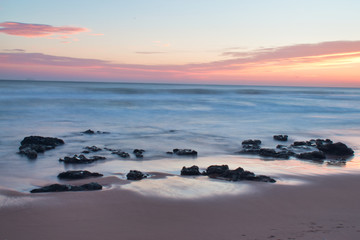 Beautiful Calming Sunrise Vacation Landscape Warm Colors Rocks on Shore Coast
