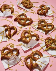 Close up of pretzel garnished with yellow sauce on pink background