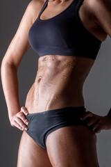 Midsection of sweating woman posing against gray background