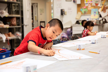 Young boy drawing in a classroom