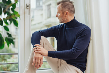 Man in blue sweater sitting on window sill