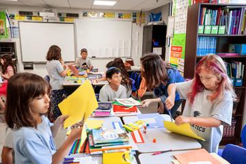 Teacher helping children in a classroom