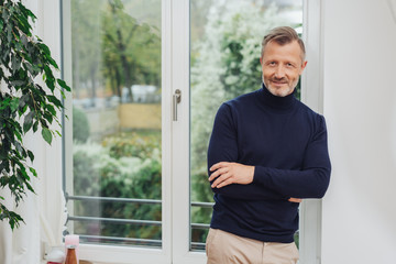 Man standing at the window and smiling