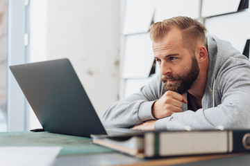 Side portrait of man looking at laptop screen