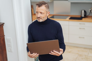 Man with big tablet, standing at home