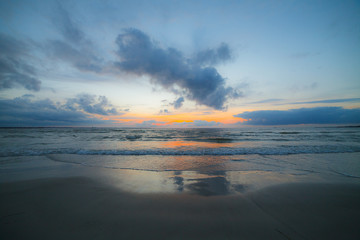 Calm Baltic sea at sunset with beautiful clouds and low waves