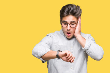Young handsome man wearing glasses over isolated background Looking at the watch time worried, afraid of getting late