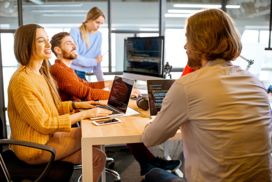 Team of a young programmers dressed casually working on computer code sitting in the modern office interior