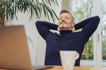Man at computer leaning back with eyes closed