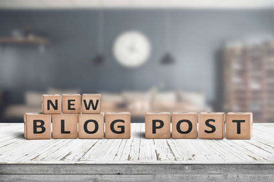 New blog post sign on a wooden desk