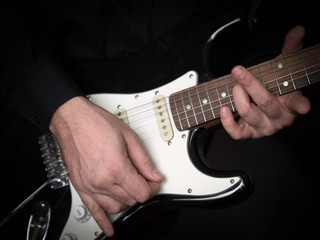 Guitarist hands playing on electric guitar, close up, selected focus