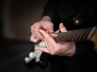 Male hands playing on electric guitar, close up, selected focus