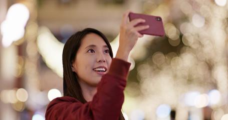 Woman take photo on Christmas tree decoration at night