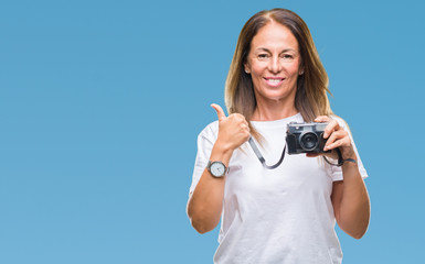 Middle age hispanic woman taking pictures using vintage photo camera over isolated background happy with big smile doing ok sign, thumb up with fingers, excellent sign