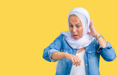Middle age eastern arab woman wearing arabian hijab over isolated background Looking at the watch time worried, afraid of getting late