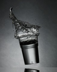 Water splashing from glass on gray background