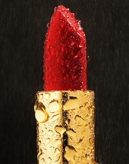 Close up of wet lipstick against black background