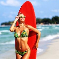 Beautiful woman in sunglasses posing with surfboard on a summer beach