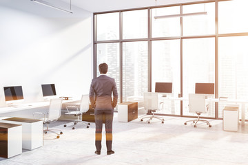 White panoramic office corner, wooden tables, man