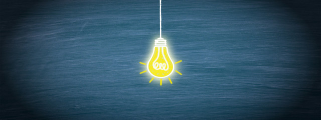 Light bulb in the middle of blue chalkboard background, copyspace for individual text
