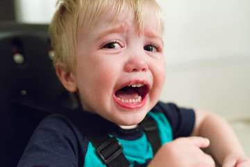 Close-up portrait of angry baby boy crying while sitting on high chair at home