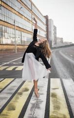 Full length of ballerina dancing on zebra crossing in city