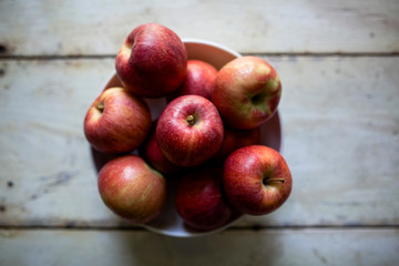 Overhead view of fresh red apples in bowl on table at home