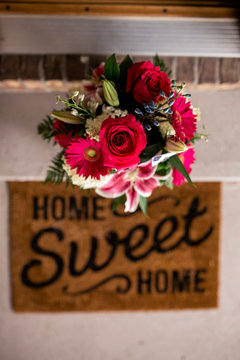 Overhead view of fresh bouquet on retaining wall by doormat at entrance