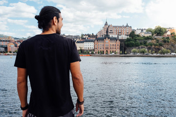 Rear view of mature man looking at river while standing in city
