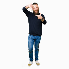 Young blond man wearing glasses and turtleneck sweater smiling making frame with hands and fingers with happy face. Creativity and photography concept.