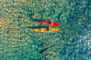 Drone shot of couple kayaking together in sea during sunny day