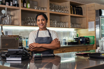 Portrait of confident female owner with arms crossed standing at bar counter in cafeteria