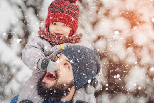happy father and baby son having fun under sunny winter snow, holiday season.