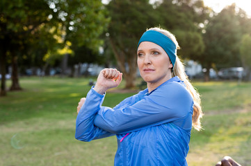Confident woman exercising while standing against trees in park