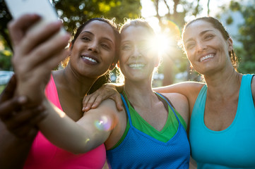 Happy female friends taking selfie with smart phone while standing in park during sunset