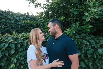 Smiling couple looking each other face to face while standing by plants in park