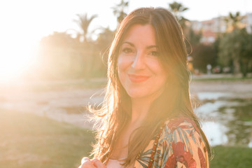 Portrait of confident smiling woman standing in park during sunset