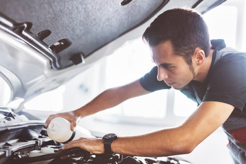Maintenance engineer doing car oil change at auto repair shop