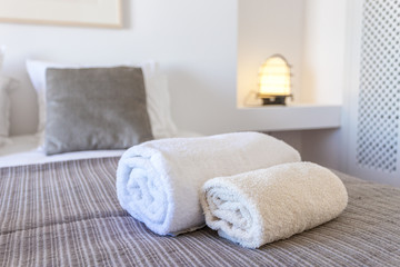 Towels for body and for hands on the bed.