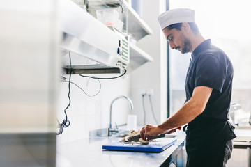 Side view of chef chopping mushrooms on cutting board in commercial kitchen at pizzeria